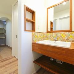 カラフルなタイルと木の色がマッチした洗面所