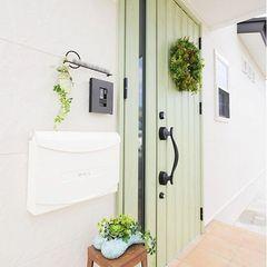 白い外壁によく似合う、優しいグリーンの玄関ドア