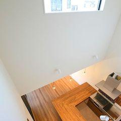 大開口の吹き抜け窓から明るい光が差し込むキッチンスペース。