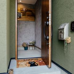 グリーンの外観に玄関土間はモルタルでシックに/四国中央市「紅と真果の家」