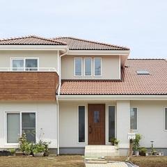 オレンジの屋根と木目の玄関が栄えわたる外観