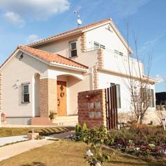 白を基調にアイアンの格子と玄関ポーチのレンガがアクセントになったプロバンス風の家