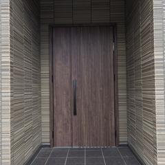 シックな色遣いで大人っぽい雰囲気が漂い質感が映えるシンプルモダンな玄関