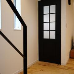 深みのあるカッコいい黒いドアが空間を引き締めてくれるナチュラルな家のリビング